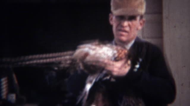 1939: Hunting man wears dead pheasant birds necklace. video