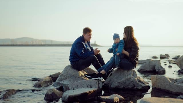 koca ve karısı suyun yakınında kayaların üzerinde oturuyor ve genç oğluyla oynuyor. birlikte olmaktan mutlu olurlar. - i̇nsan sırtı stok videoları ve detay görüntü çekimi