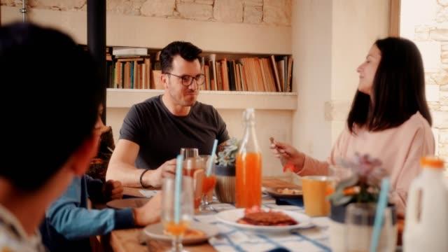 mann und frau, die morgens beim frühstück mit kindern - brunch stock-videos und b-roll-filmmaterial
