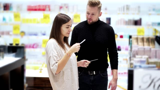 Husband and wife in cosmetics store choose perfume, woman sprays perfume