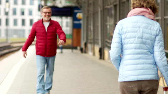 Husband and wife on a spring walk through the city. Look at the frame, hug and laugh. Date mature couple