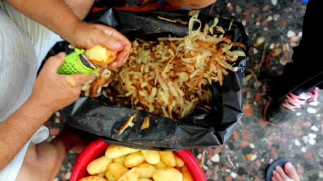 mann und frau schälen kartoffeln im restaurant. küche zu arbeiten. essen zubereiten - geschält stock-videos und b-roll-filmmaterial