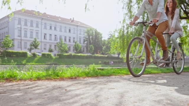 CS Husband and wife riding a tandem bicycle through a park