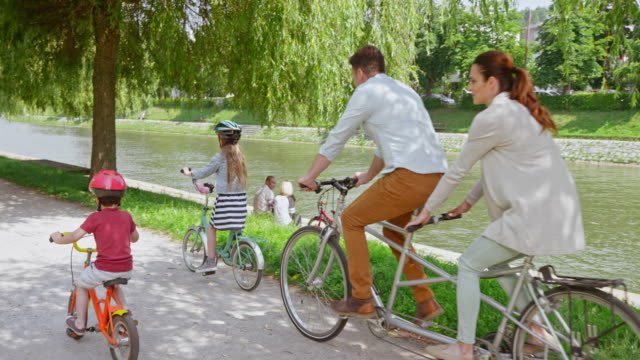 SLO MO CS Husband and wife riding a tandem bike in the park and their two children riding alongside them Slow motion wide crane shot of two children riding their bikes in the city park and their mom and dad riding on tandem bike behind them. Shot in Slovenia. cycle vehicle stock videos & royalty-free footage