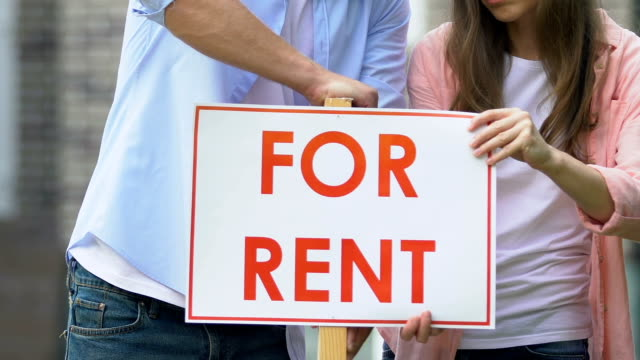Husband and wife setting for rent sign and hugging outdoors, private property Husband and wife setting for rent sign and hugging outdoors, private property house rental stock videos & royalty-free footage