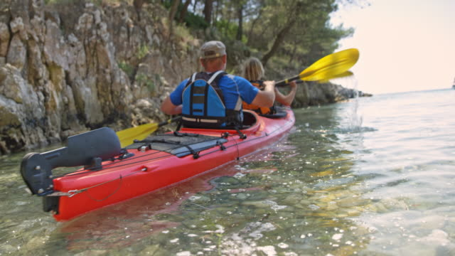 Husband and wife taking off from the beach in their sea kayak