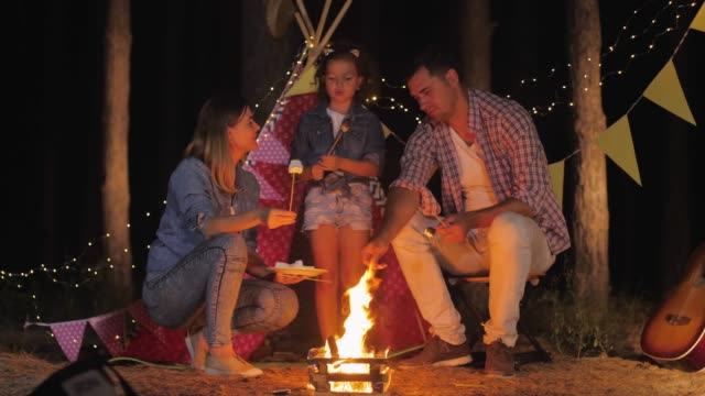 husband and wife with child happily spend time in family atmosphere eating fried marshmallows at bonfire during picnic in night forest near wigwam