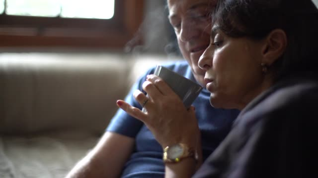 husband embracing wife with fever while drink her hot tea - зрелая пара стоковые видео и кадры b-roll