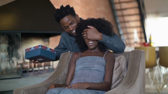 stockvideo's en b-roll-footage met man het maken van een verrassing het geven van een cadeautje aan zijn vrouw thuis - uitwisselen
