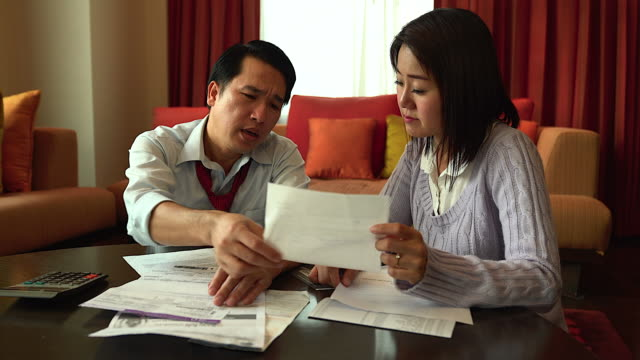 husband or father calculating his bills while his family are on the sofa.seriously with financial problem. - modulo documento video stock e b–roll