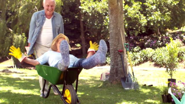 vídeos de stock, filmes e b-roll de marido empurrando sua esposa em um carrinho de mão - jardinagem