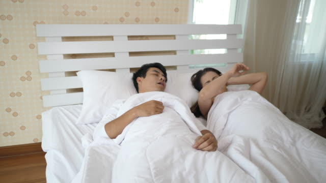 Husband snore near his wife on the bed - video