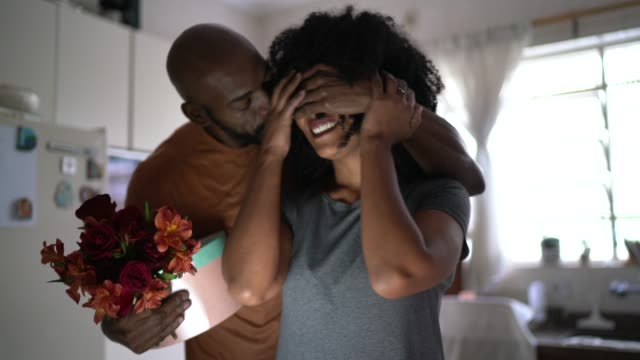 Husband surprising his wife with flowers and present at home