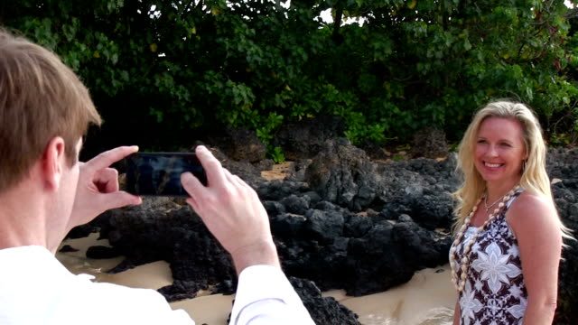 Husband takes picture of wife on beach video