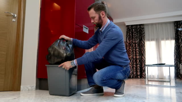 husband taking trash domestic chores - stock video - baffo peluria del viso video stock e b–roll