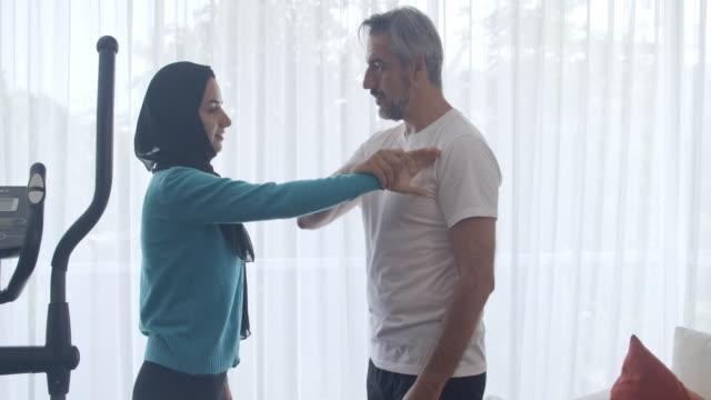 vídeos de stock, filmes e b-roll de marido ensinando sua esposa auto-defesa na sala de estar. estilo oriente médio. - autodefesa
