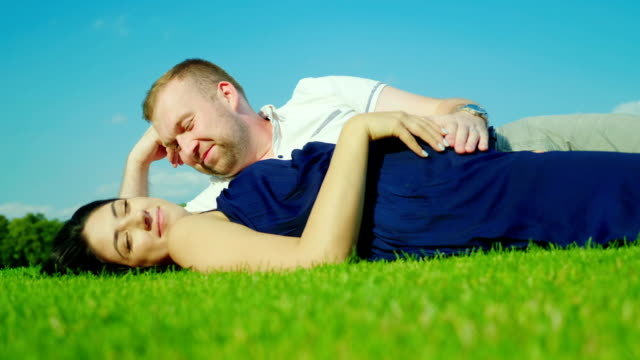 Husband with a pregnant wife is lying on the green grass. Against the background of the blue sky video