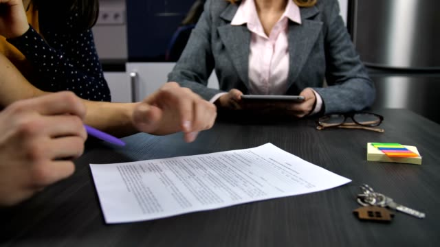 Husband's hands signing mortgage contract Midsection of realtor and family couple sitting at table. Husband's hands reading house purchase agreement, putting signature and shaking hands with agent. Family signing mortgage contract. Dolly shot loan stock videos & royalty-free footage