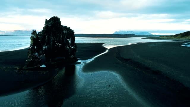 stockvideo's en b-roll-footage met hvitserkur - iconische zee stapel op vulkanisch zwart strand. vogel met het vliegen voor drone - boog architectonisch element