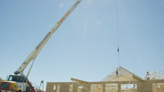 A Hydraulic Crane Helps Construction Workers Frame a House on a Construction Site on a Clear, Sunny Day