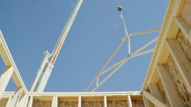 vidéos et rushes de une grue hydraulique abaisse une armature en bois encadrée de toit en place sur une maison encadrée à un chantier de construction sur une journée claire et ensoleillée - abaisser