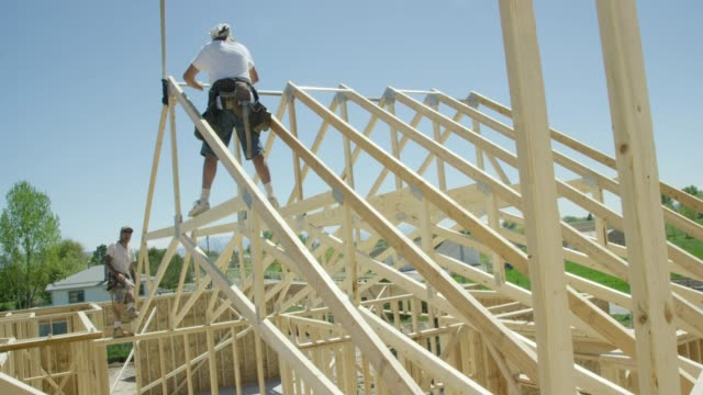 A Hydraulic Crane Lowers a Framed Wooden Roof Truss into Place While Two Caucasian Male Construction Workers in Their Forties Attach It to the Structure Using Hammers and Nails While Framing a House on a Clear, Sunny Day
