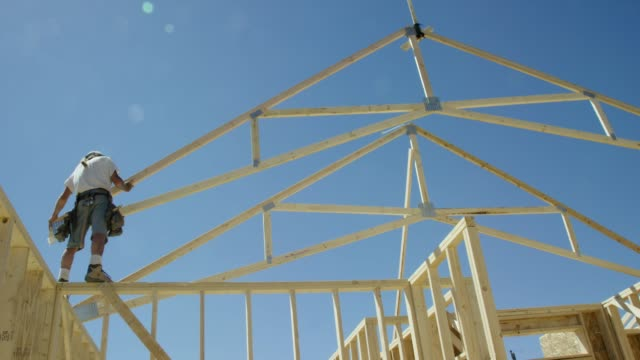 a hydraulic crane lowers a framed wooden roof truss to a caucasian male construction worker in his forties who guides it into place while framing a house on a clear, sunny day - proprietario d'immobili video stock e b–roll