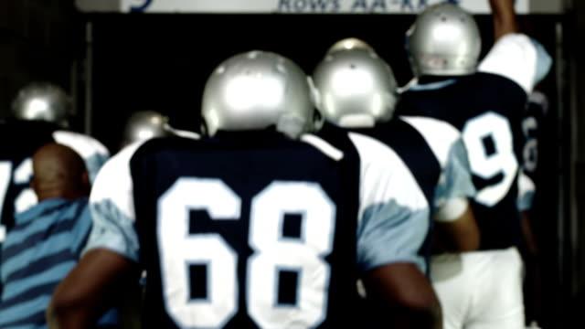 宣伝を開くサッカー チームはトンネルの下カメラから離れて歩く - 入る点の映像素材/bロール