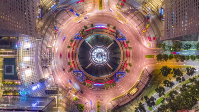 Hyper Lapse of Drone, Aerial Panorama view at Night time-lapse at fountain of wealth roundabout and traffic car light, at center of business district area, Singapore