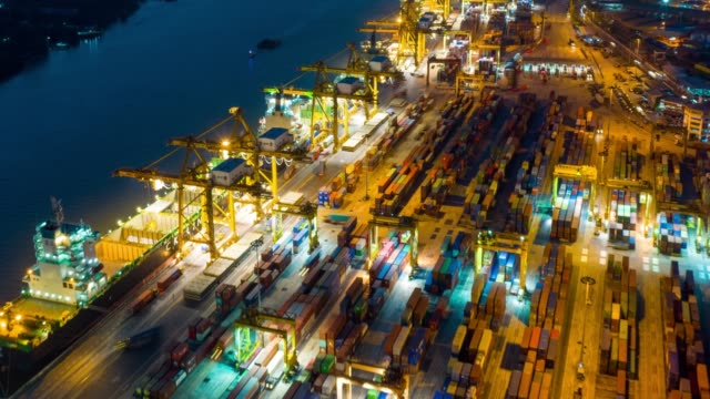 vídeos de stock e filmes b-roll de hyper lapse of international port with crane loading containers in import export business logistics. - drone shipyard night