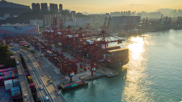 vídeos de stock e filmes b-roll de hyper lapse or dronelapse of international port with crane loading containers in import export business logistics at hong kong - drone shipyard night