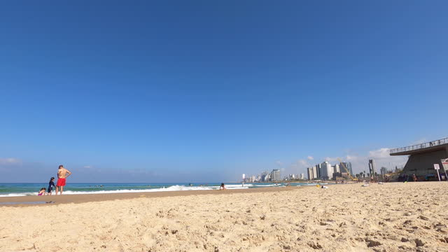 TEL AVIV, ISRAEL - OCTOBER 09, 2020: Hyper time lapse of a beach with the view of Tel Aviv skyline