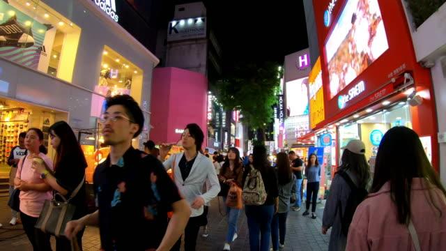 vídeos de stock, filmes e b-roll de hyper timelapse em myeong-dong market. people que andam em uma rua de compra na noite, seoul, coreia do sul - coreia