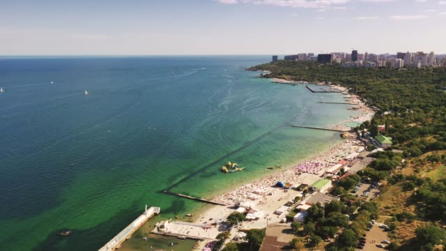 Hyperlapse aerial shot of sea coast line during summer sunny day, boats are passing by