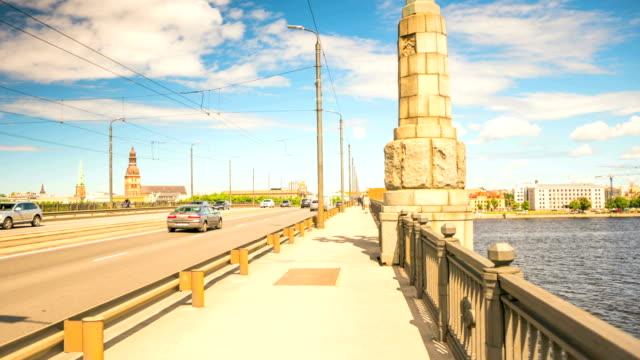 vídeos de stock, filmes e b-roll de um hyperlapse de um horizonte de riga cidade do outro lado de um rio daugava, em um dia nublado 4k - países bálticos