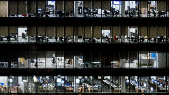 hyperlapse of corporate life in glass office center at night, timelapse background. - edificio adibito a uffici video stock e b–roll