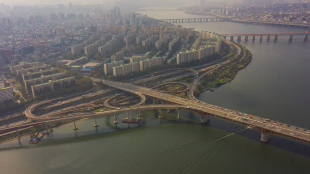 Hyperlapse or Dronelapse Aerial view of Highway road junctions. The Intersecting freeway road overpass of Seoul downtown city skyline with vehicle on expressway and bridge cross over Han river in Seoul city, South Korea. Hyperlapse or Dronelapse Aerial view of Highway road junctions. The Intersecting freeway road overpass of Seoul downtown city skyline with vehicle on expressway and bridge cross over Han river in Seoul city, South Korea. namsan seoul stock videos & royalty-free footage