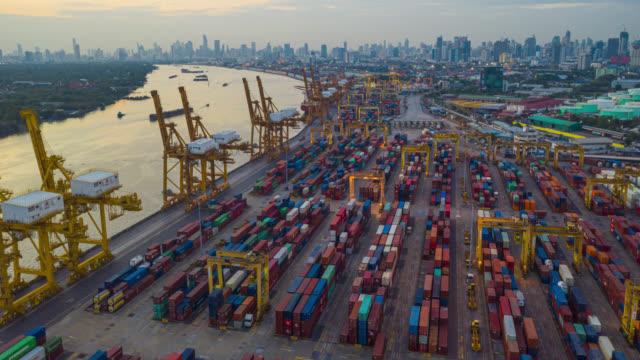 Hyperlapse or Dronelapse aerial view of international port with Crane loading containers in import export business logistics. Hyperlapse or Dronelapse aerial view of international port with Crane loading containers in import export business logistics. commercial dock stock videos & royalty-free footage