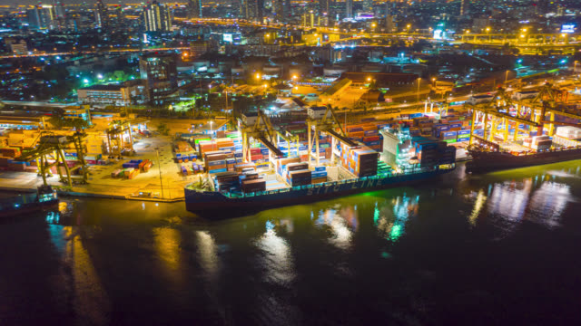 Hyperlapse or Dronelapse aerial view of international port with Crane loading containers in import export business logistics.