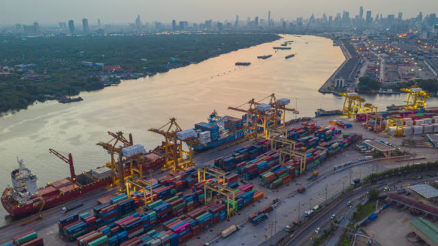 vídeos de stock e filmes b-roll de hyperlapse or dronelapse aerial view of international port with crane loading containers in import export business logistics. - drone shipyard night