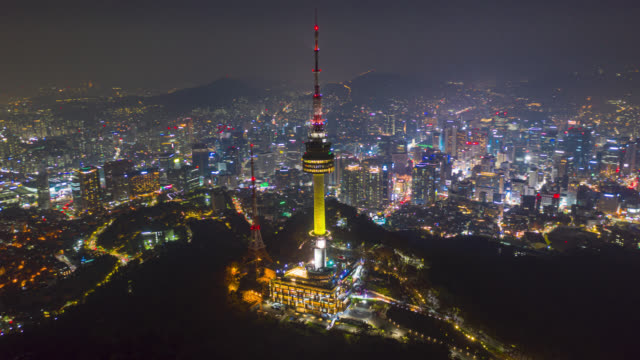 hyperlapse o dronelapse vista aerea della n seoul tower nello skyline del centro di seoul con sentieri leggeri sulla montagna samson di notte nella città di seoul, in corea del sud. - corea video stock e b–roll