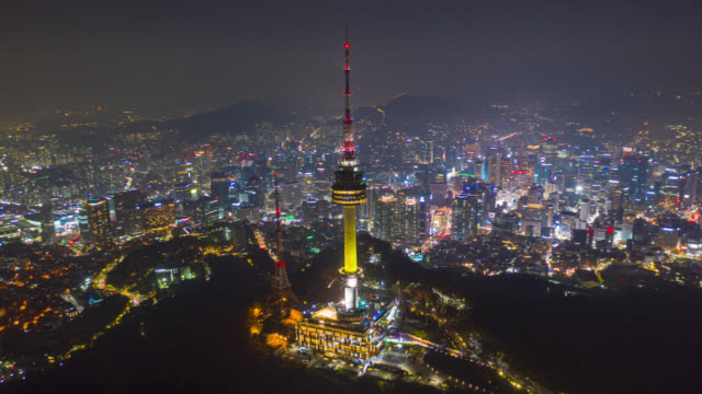 Hyperlapse or Dronelapse Aerial view of N Seoul Tower in Seoul downtown city skyline with light trails on Samson mountain at night in Seoul city, South Korea. Hyperlapse or Dronelapse Aerial view of N Seoul Tower in Seoul downtown city skyline with light trails on Samson mountain at night in Seoul city, South Korea. south korea stock videos & royalty-free footage