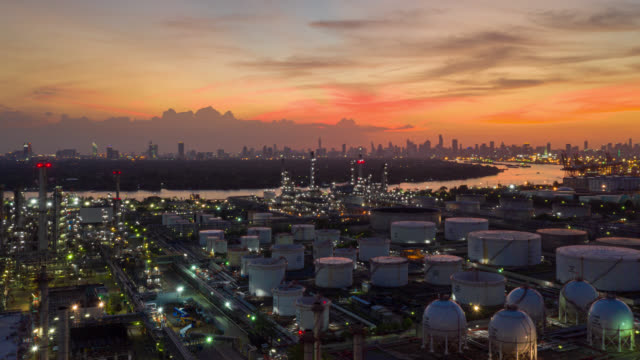 日没時に国際港近くの石油精製所のハイパーラプスまたはドローンラプス空中写真。日没時の製油所工場。製油所工場およびタンク - 気体点の映像素材/bロール