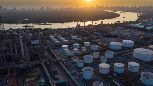 Hyperlapse or Dronelapse aerial view of oil refinery near international port at sunset. Refinery plant at sunset. refinery factory and tank