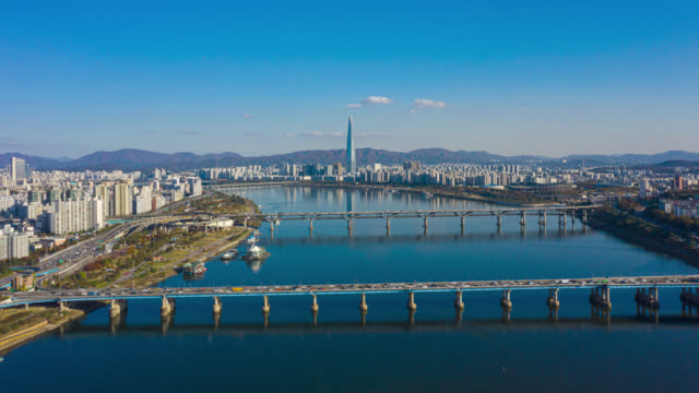 Hyperlapse or Dronelapse Aerial view of Seoul downtown city skyline with vehicle on expressway and bridge cross over Han river in Seoul city, South Korea. Hyperlapse or Dronelapse Aerial view of Seoul downtown city skyline with vehicle on expressway and bridge cross over Han river in Seoul city, South Korea. namsan seoul stock videos & royalty-free footage