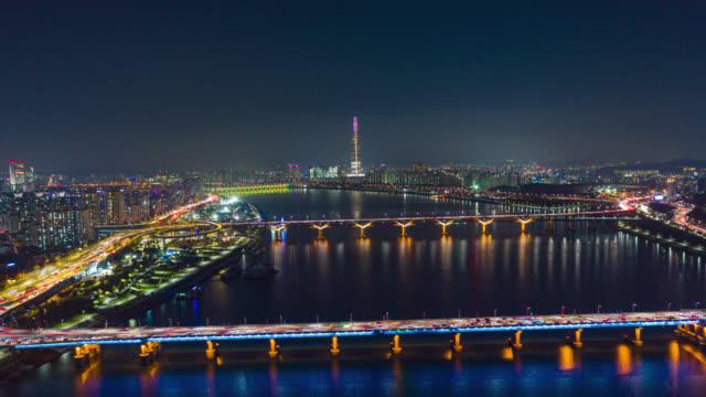 vídeos de stock, filmes e b-roll de vista aérea hyperlapse ou dronelapse do horizonte da cidade de seul com trilhas leves na via expressa e ponte cruza sobre o rio han à noite na cidade de seul, coreia do sul. - coreia