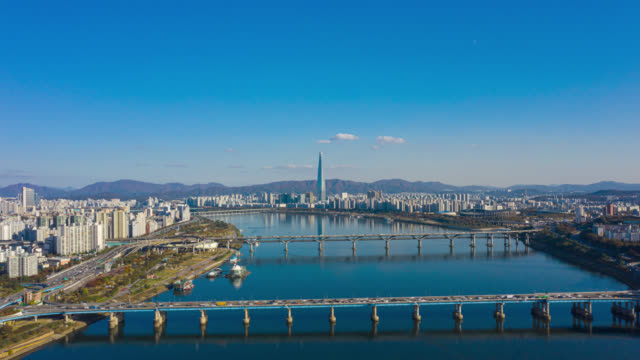 Hyperlapse or Dronelapse Aerial view of Seoul downtown city skyline with car driving on expressway and bridge cross over Han river in Seoul city, South Korea. Hyperlapse or Dronelapse Aerial view of Seoul downtown city skyline with car driving on expressway and bridge cross over Han river in Seoul city, South Korea. namsan seoul stock videos & royalty-free footage