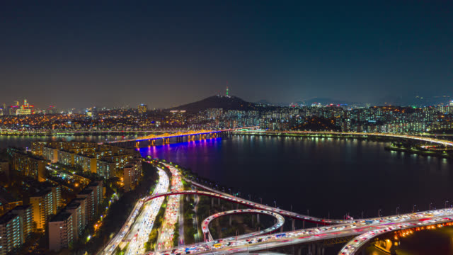 Hyperlapse or Dronelapse Aerial view of Seoul downtown city skyline with light trails on expressway and bridge cross over Han river at night in Seoul city, South Korea.