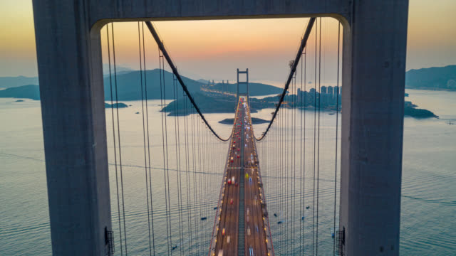 Hyperlapse or Dronelapse Aerial view of Traffic of car at Tsing ma bridge in Tsing yi area of Hong Kong at sunset. Day to night timelapse
