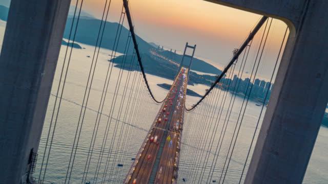 vídeos de stock, filmes e b-roll de visão aérea hyperlapse ou dronelapse do tráfego de carros na ponte tsing ma em tsing yi área de hong kong ao pôr do sol. timelapse do dia para a noite - ponte